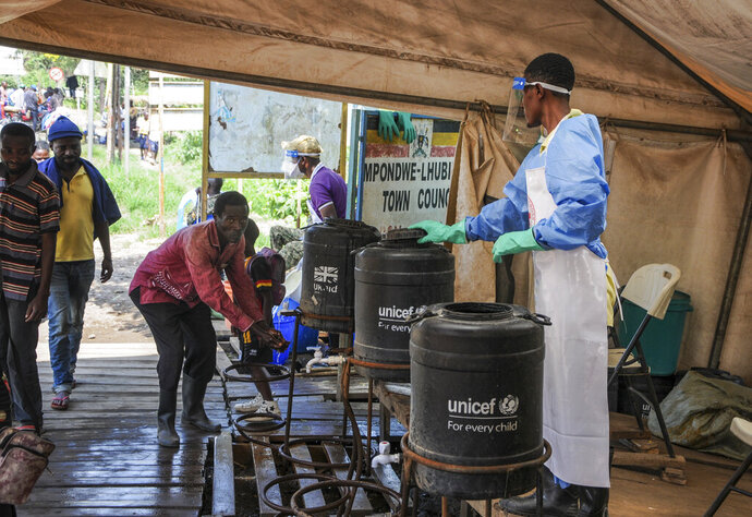 FILE - In this Friday, June 14, 2019 file photo, people coming from Congo wash their hands with chlorinated water to prevent the spread of Ebola infection, at the Mpondwe border crossing with Congo. Ugandan health authorities on Thursday, Aug. 29, 2019 said a 9-year-old Congolese child has tested positive for Ebola in Uganda, after being identified and screened at the official Mpondwe border crossing, and was then taken to an isolation unit in the Ugandan border town of Bwera in Kasese district. (AP Photo/Ronald Kabuubi, File)