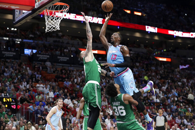 Miami Heat forward Bam Adebayo (13) goes to the basket as Boston Celtics center Daniel Theis (27) and guard Marcus Smart (36) defend during the first half of an NBA basketball game, Tuesday, Jan. 28, 2020, in Miami. Adebayo was called for an offensive foul on the play. (AP Photo/Lynne Sladky)