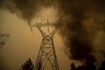 FILE - In this Nov. 9, 2018, file photo, smoke billows around power transmission lines as the Camp Fire burns in Big Bend, Calif. Experts say it's hard to know whether keeping millions of Californians in the dark prevented a catastrophic wildfire. The question takes on new significance after authorities said Friday, Oct. 11, 2019, that a man in his 60s who relied on oxygen died 12 minutes after losing electricity in a planned outage by Pacific Gas & Electric Co., east of Sacramento. (AP Photo/Noah Berger, File)