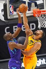 Utah Jazz center Rudy Gobert (27) blocks the shot from Charlotte Hornets center Bismack Biyombo, left, in the first half during an NBA basketball game Monday, Feb. 22, 2021, in Salt Lake City. (AP Photo/Rick Bowmer)