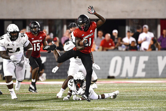 Louisville wide receiver Josh Johnson (11) fights his way out of the grasp of Central Florida defensive back Quadric Bullard (37) during the second half of an NCAA college football game in Louisville, Ky., Friday, Sept. 17, 2021. (AP Photo/Timothy D. Easley)