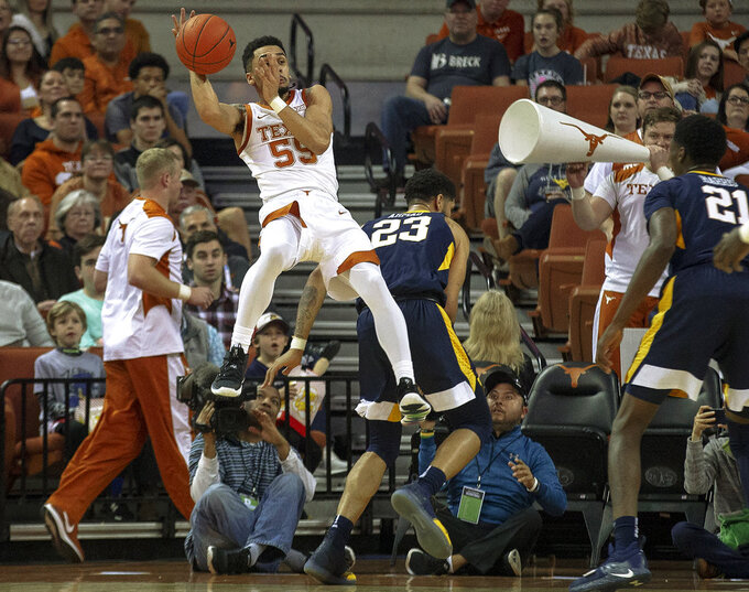 Texas guard Elijah Mitrou-Long (55) saves the ball from going out of bounds against West Virginia during an NCAA college basketball game on Saturday, Jan. 5, 2019, in Austin, Texas. (Nick Wagner/Austin American-Statesman via AP)