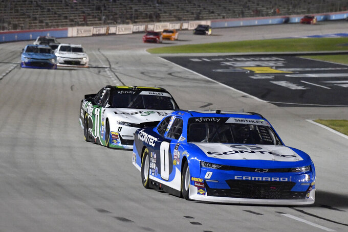 Garrett Smithley (0) and Justin Haley (11) head into Turn 1 during NASCAR Xfinity auto race at Texas Motor Speedway in Fort Worth, Texas, Saturday, Nov. 2, 2019. (AP Photo/Larry Papke)