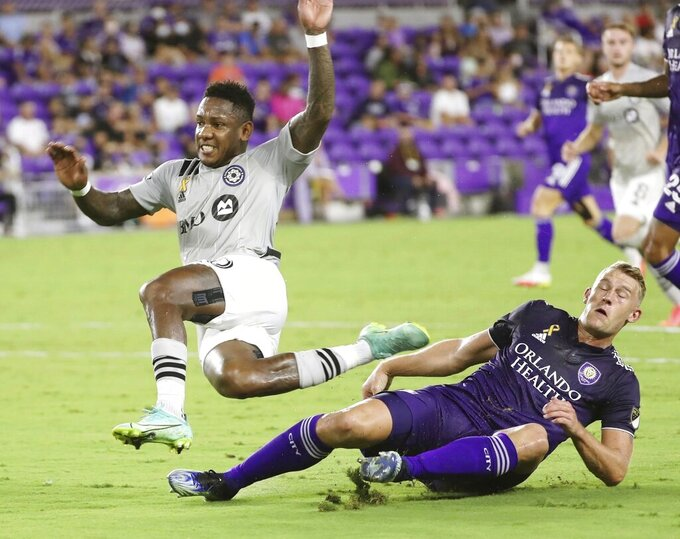 CF Montreal's Romell Quioto, left, leaps over Orlando City's Robin Jansson during an MLS soccer match in Orlando, Fla., Wednesday, Sept. 15, 2021. (Stephen M. Dowell/Orlando Sentinel via AP)