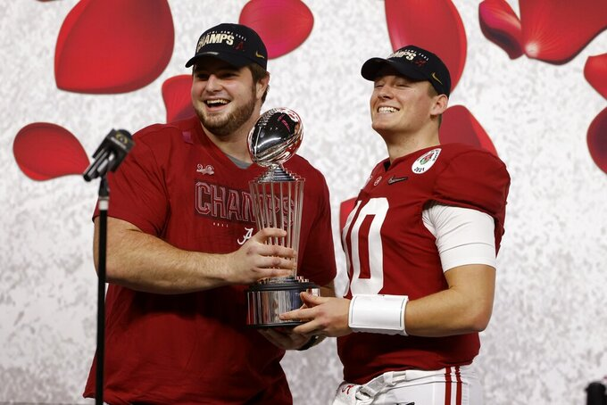 Alabama offensive lineman Landon Dickerson and quarterback Mac Jones hold the trophy after their win against Notre Dame in the Rose Bowl NCAA college football game in Arlington, Texas, Friday, Jan. 1, 2021. (AP Photo/Ron Jenkins)
