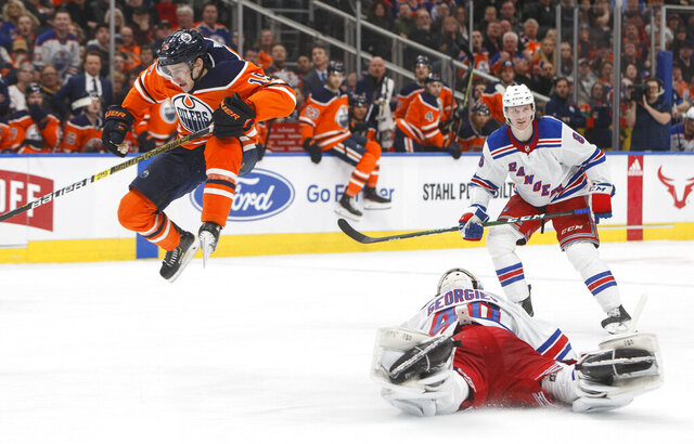 New York Rangers goalie Alexandar Georgiev (40) dives for the puck as Edmonton Oilers' Josh Archibald (15) jumps over during second period NHL hockey action in Edmonton, Alberta, Tuesday, Dec. 31, 2019. (Jason Franson/The Canadian Press via AP)