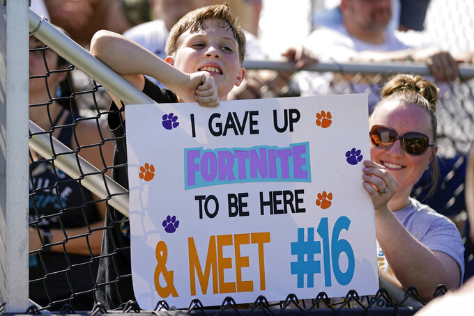 Jacksonville Jaguars fans hold up a sign hoping that quarterback Trevor Lawrence (16) will take notice during NFL football practice, Saturday, July 31, 2021, in Jacksonville, Fla. (AP Photo/John Raoux)