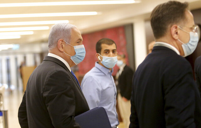Israeli Prime Minister Benjamin Netanyahu, left, wears a protective face mask, as he makes his way to attend the swearing in ceremony of his new government, at the Knesset, Israel's parliament, in Jerusalem, Sunday, May 17, 2020. Netanyahu is finally swearing in his new government after three deadlocked and divisive elections, a year and a half of political paralysis and another three-day delay because of political infighting in his Likud party over coveted Cabinet posts. (Alex Kolomiensky/Yedioth Ahronoth/Pool via AP)