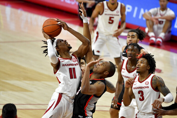 Arkansas guard Jalen Tate (11) tries to drive past Georgia defender Christian Brown (3) during the second half of an NCAA college basketball game Saturday, Jan. 9, 2021, in Fayetteville, Ark. (AP Photo/Michael Woods)