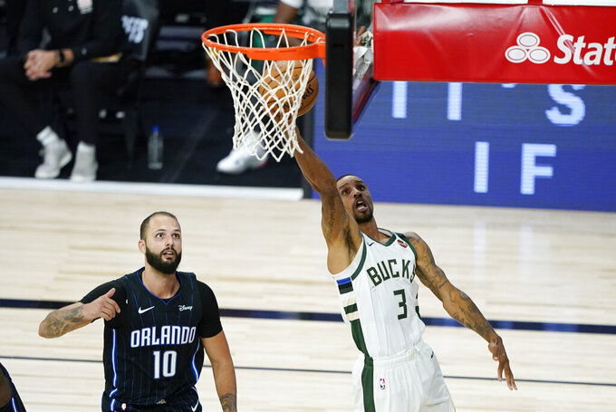 Milwaukee Bucks' George Hill (3) drives to the basket past Orlando Magic's Evan Fournier (10) during the second half of an NBA basketball first round playoff game Monday, Aug. 24, 2020, in Lake Buena Vista, Fla. (AP Photo/Ashley Landis, Pool)