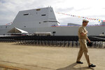 FILE - A member of the U.S. Navy walks past the future USS Zumwalt in Baltimore, in this Thursday, Oct. 13, 2016, file photo. The electric-drive, angular Zumwalt was commissioned into service, but its 155mm advanced gun system is being scrapped because its munitions are too expensive. (AP Photo/Patrick Semansky, File)