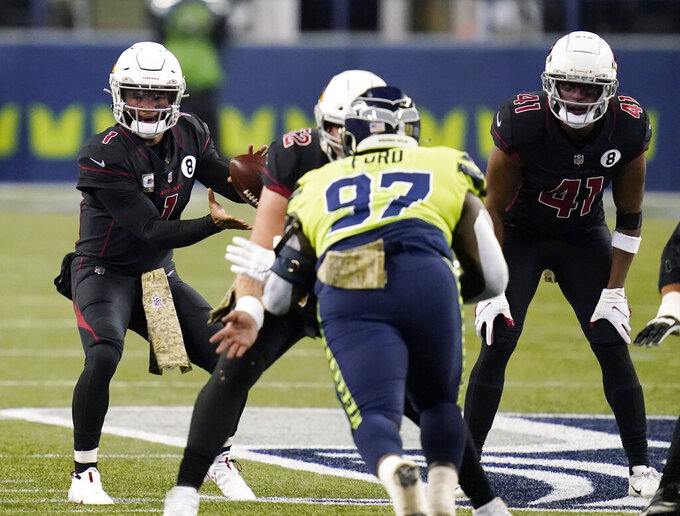 Arizona Cardinals quarterback Kyler Murray (1), left, takes a snap against the Seattle Seahawks during the second half of an NFL football game, Thursday, Nov. 19, 2020, in Seattle. (AP Photo/Elaine Thompson)