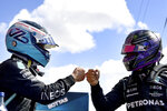 Mercedes driver Lewis Hamilton of Britain, right, congratulates Mercedes driver Valtteri Bottas of Finland after he clocked the fastest time during the qualifying session ahead of the Portugal Formula One Grand Prix at the Algarve International Circuit near Portimao, Portugal, Saturday, May 1, 2021. The Portugal Grand Prix will be held on Sunday. (Gabriel Buoys/Pool via AP)