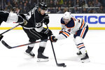 Los Angeles Kings left wing Dustin Brown, left, shoots with Edmonton Oilers defenseman Kris Russell, right, defending during the second period of an NHL hockey game in Los Angeles, Thursday, Nov. 21, 2019. (AP Photo/Alex Gallardo)