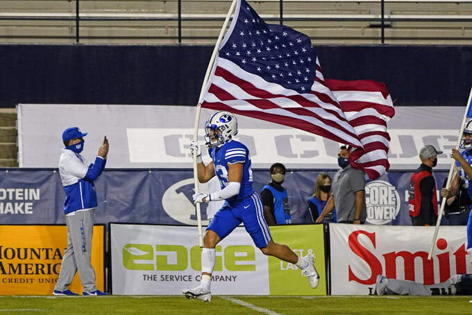 A BYU player carries a U.S. flag onto the field at the start of the team's NCAA college football game against Troy on Saturday, Sept. 26, 2020, in Provo, Utah. (AP Photo/Rick Bowmer, Pool)