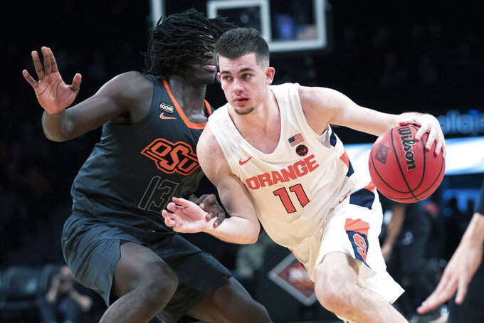Syracuse guard Joseph Girard III (11) drives against Oklahoma State guard Isaac Likekele (13) during the second half of an NCAA college semi final basketball game in the NIT Season Tip-Off tournament, Wednesday, Nov. 27, 2019, in New York. Oklahoma State won 86-72. (AP Photo/Mary Altaffer)