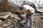 Lyle Stewart looks through burned debris at his destroyed house at Nerrigundah, Australia, Monday, Jan. 13, 2020, after a wildfire ripped through the town on New Year's Eve. The tiny village of Nerrigundah in New South Wales has been among the hardest hit by Australia's devastating wildfires, with about two thirds of the homes destroyed and a 71-year-old man killed. (AP Photo/Rick Rycroft)