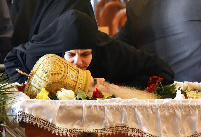 A nun kisses the Bishop Amfilohije's body during the liturgy and funeral in the main temple in the capital Podgorica, Montenegro, Sunday, Nov. 1, 2020. Bishop Amfilohije died on Friday after contracting the coronavirus weeks ago. A mass funeral on Sunday was held for the popular head of the Serbian Orthodox Church in Montenegro in violation of restrictions that are in place against the new coronavirus. (AP Photo/Risto Bozovic)