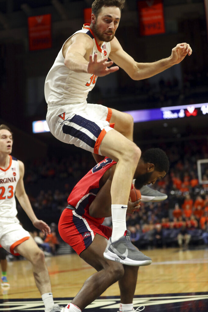 Virginia forward Jay Huff (30) leaps over Stony Brook guard Andrew Garcia (23) during an NCAA college basketball game in Charlottesville, Va., Wednesday, Dec. 18, 2019. (AP Photo/Andrew Shurtleff)