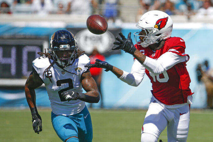 Arizona Cardinals wide receiver DeAndre Hopkins, right, makes a reception in front of Jacksonville Jaguars defensive back Rayshawn Jenkins (2) during the first half of an NFL football game, Sunday, Sept. 26, 2021, in Jacksonville, Fla. (AP Photo/Stephen B. Morton)