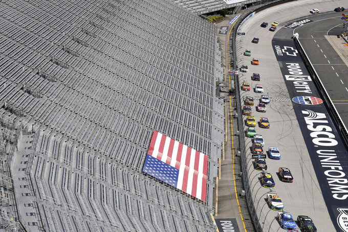 FILE - In this May 31, 2020, file photo, cars speed past empty stands during a NASCAR Cup Series auto race at Bristol Motor Speedway in Bristol, Tenn. Tennis and golf tournaments could be in real financial trouble if they are held without spectators because of the coronavirus pandemic. The biggest team leagues such as the NFL and NBA seem to be in good shape because they derive most of their money from TV contracts worth billions each season. NASCAR also relies mainly on broadcast rights fees. (AP Photo/Mark Humphrey, File)
