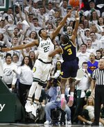 Michigan guard Zavier Simpson (3) releases a hook shot as Michigan State forward Xavier Tillman (23) defends during the first half of an NCAA college basketball game Saturday, March 9, 2019, in East Lansing, Mich. (AP Photo/Carlos Osorio)