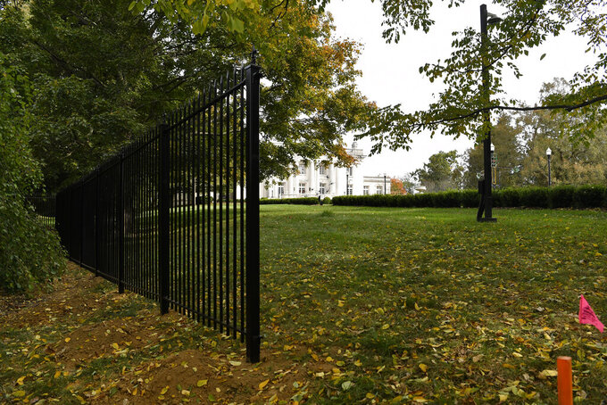 A security fence is being installed around the Governors Mansion on the grounds of the Kentucky State Capitol in Frankfort, Ky., Friday, Oct. 9, 2020. Security is being increased following a plot to kidnap the Governor of Michigan, and Andy Beshear, a Democrat, was hanged in effigy from a tree during a May protest against his COVID-19 restrictions on the state Capitol grounds in Frankfort. (AP Photo/Timothy D. Easley)