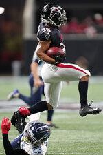 Atlanta Falcons cornerback Avery Williams (35) leaps over Tennessee Titans cornerback Caleb Farley (23) during the second half of a preseason NFL football game, Friday, Aug. 13, 2021, in Atlanta. (AP Photo/Brynn Anderson)