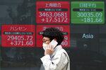 A man wearing a protective mask walks in front of an electronic stock board at a securities firm Friday, March 19, 2021, in Tokyo. Asian stock markets followed Wall Street lower on Friday after rising U.S. bond yields pulled stocks lower, dampening enthusiasm driven by the Federal Reserve's promise of low interest rates. (AP Photo/Eugene Hoshiko)