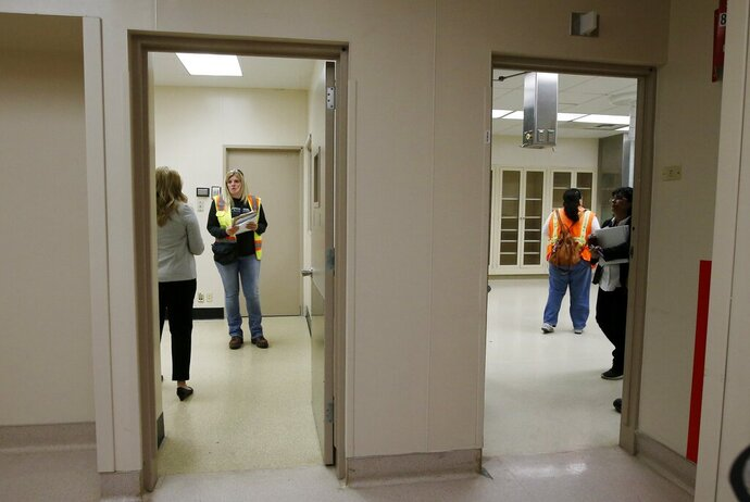 A group from the U.S. Army Corps of Engineers and the Arizona health department tour the currently closed St. Luke's Medical Center hospital to see the viability of reopening the facility for possible future use due to the coronavirus Wednesday, March 25, 2020, in Phoenix. (AP Photo/Ross D. Franklin)