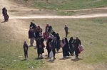 In this Sunday, Feb. 10, 2019 image from video provided by Hawar News Agency, ANHA, an online Kurdish news service, civilians flee fighting near Baghouz, Syria. Fierce fighting was underway Monday between U.S.-backed Syrian forces and the Islamic State group around the extremists' last foothold in eastern Syria. The capture of the IS-held village of Baghouz and nearby areas would mark the end of a four-year global war to end IS' territorial hold over large parts of Syria and Iraq, where the group established its self-proclaimed