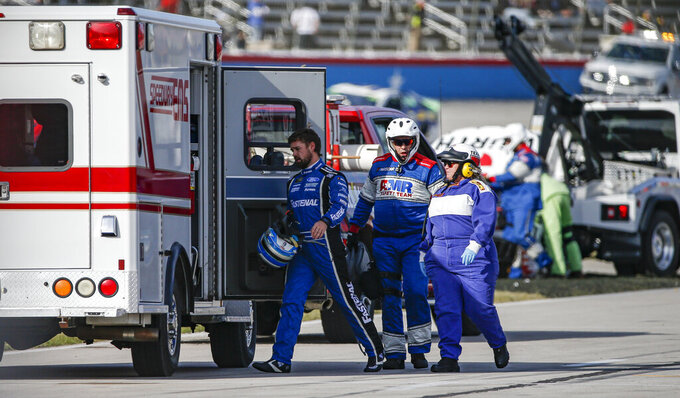 Ricky Stenhouse Jr., left, is escorted to an ambulance as a precaution after wrecking exiting turn four during a NASCAR auto race at Texas Motor Speedway, Sunday, Nov. 3, 2019, in Fort Worth, Texas. (AP Photo/Brandon Wade)