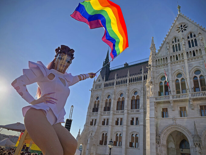 FILE - In this file photo dated June. 14, 2021, an unidentified drag queen waves a rainbow flag during an LGBT rights demonstration in front of the Hungarian Parliament building in Budapest, Hungary. Hungary's government has called for a national referendum in defence of what it calls child protection measures that many have criticised as an attack on LGBT rights. (AP Photo/Bela Szandelszky, FILE)