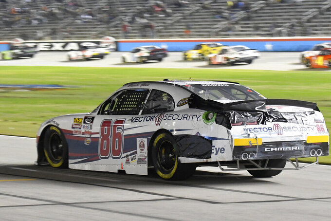 Brandon Brown leads his damaged vehicle down pit road during a NASCAR Xfinity auto race at Texas Motor Speedway in Fort Worth, Texas, Saturday, Nov. 2, 2019. (AP Photo/Randy Holt)