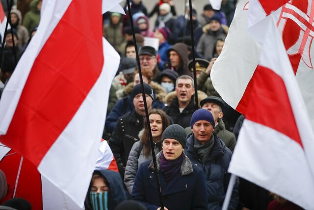 Demonstrators with old Belarusian flags listen to a speaker during a protest against closer integration with Russia, which protesters fear could erode the post-Soviet independence of Belarus, in downtown in Minsk, Belarus, Saturday, Dec. 21, 2019. The presidents of Belarus and Russia have met to discuss deeper economic ties between the two close allies amid mounting concerns in Minsk that Moscow ultimately wants to subdue its neighbor. (AP Photo/Sergei Grits)