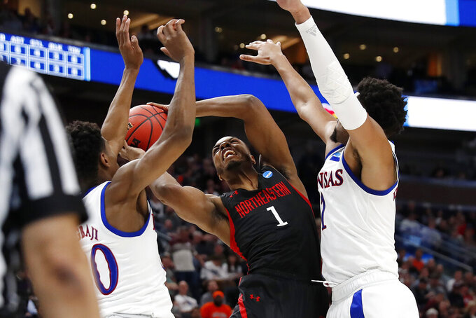 Northeastern guard Shawn Occeus (1) is guarded by Kansas guard Ochai Agbaji, left, and forward Dedric Lawson, right, during the second half of a first-round game in the NCAA men's college basketball tournament Thursday, March 21, 2019, in Salt Lake City. (AP Photo/Jeff Swinger)