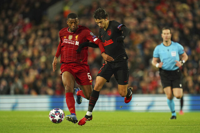 Liverpool's Georginio Wijnaldum, left, fights for the ball with Atletico Madrid's Joao Felix during a second leg, round of 16, Champions League soccer match between Liverpool and Atletico Madrid at Anfield stadium in Liverpool, England, Wednesday, March 11, 2020. (AP Photo/Jon Super)