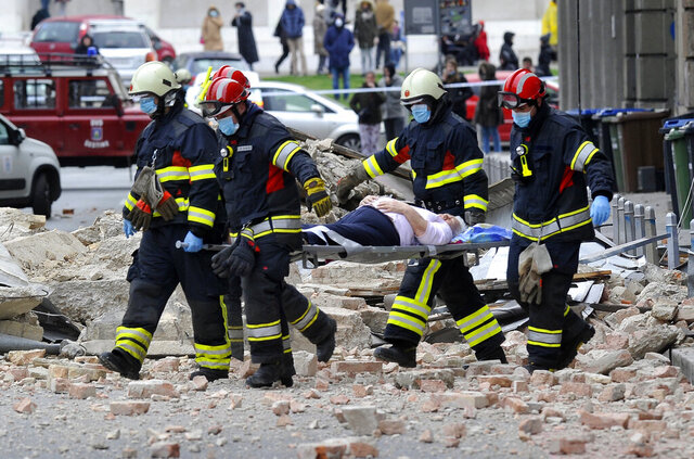 FILE - In this March 22, 2020, file photo, firefighters carry a person on a stretcher after a strong earthquake in Zagreb, Croatia. The virus outbreak is compromising the ability of nations to prepare for natural disasters and deal with the aftermath. Every year, the world contends with devastating typhoons, wildfires, tsunamis and earthquakes. (AP Photo/File)