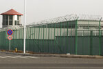 FILE - In this Monday, Dec. 3, 2018, file photo, a guard tower and barbed wire fence surround a detention facility in the Kunshan Industrial Park in Artux in western China's Xinjiang region. The Associated Press has found that the Chinese government is carrying out a birth control program aimed at Uighurs, Kazakhs and other largely Muslim minorities in Xinjiang, even as some of the country's Han majority is encouraged to have more children. The measures include detention in prisons and camps, such as this facility in Artux, as punishment for having too many children. (AP Photo/Ng Han Guan, File)