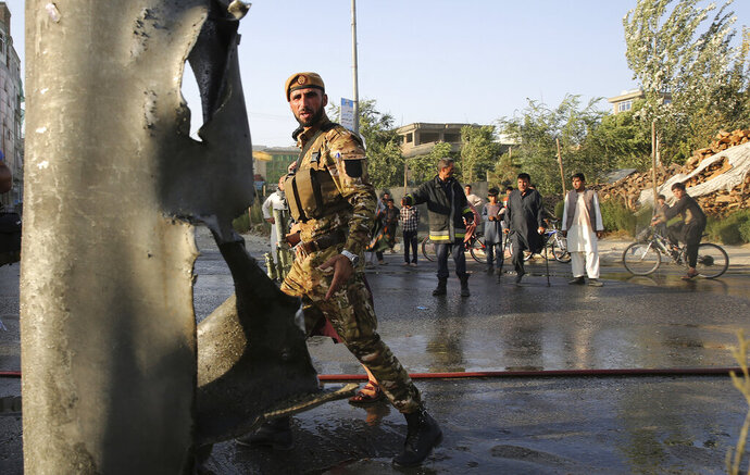 An Afghan police officer stands guard near the site of a deadly explosion in Kabul, Afghanistan, Tuesday, Aug. 6, 2019. A magnetic bomb was placed on a van carrying employees of the Interior Ministry's counter-narcotics division. In Kabul on Tuesday, a bomb targeted a van carrying employees of the Interior Ministry's counter-narcotics division. The blast killed five people and wounded another seven, Interior Ministry spokesman Nasrat Rahimi said. No one immediately claimed responsibility for the attack. (AP Photo/Rafiq Maqbool)
