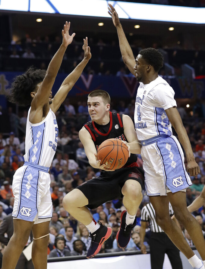Louisville's Ryan McMahon, center, drives between North Carolina's Coby White, left, and Brandon Robinson, right, during the second half of an NCAA college basketball game in the Atlantic Coast Conference tournament in Charlotte, N.C., Thursday, March 14, 2019. (AP Photo/Chuck Burton)