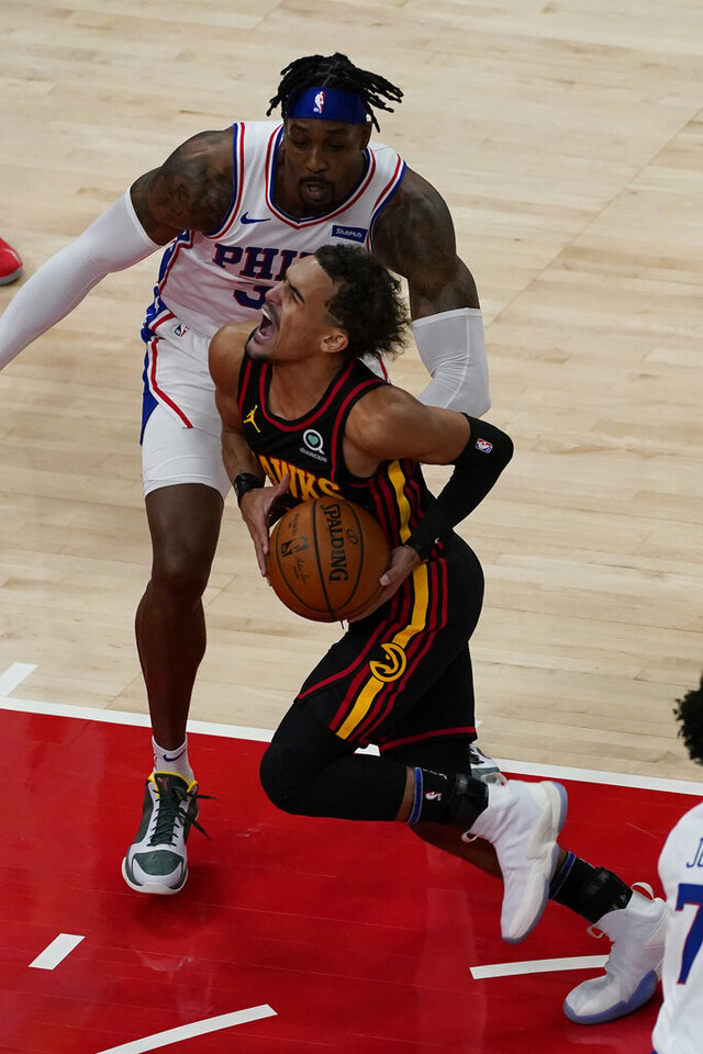 Atlanta Hawks guard Trae Young (11) drives against Philadelphia 76ers center Dwight Howard (39) during the first half of an NBA basketball game Monday, Jan. 11, 2021, in Atlanta. (AP Photo/John Bazemore)