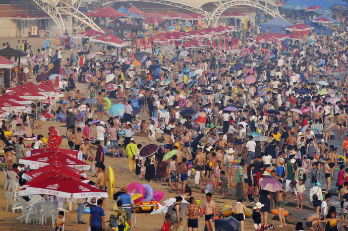 FILE - In this July 12, 2017, file photo, visitors flock to a beach in Qingdao in eastern China's Shandong Province. China's population crept past 1.4 billion in 2019 for the first time, even as the birthrate continues to fall. (Chinatopix via AP, File)