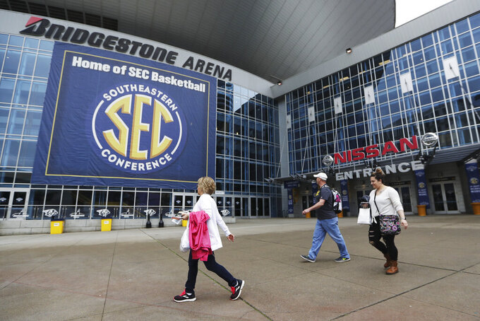 People walk across the empty plaza at the entrance to Bridgestone Arena, the site of the NCAA basketball Southeastern Conference Tournament, Thursday, March 12, 2020, in Nashville, Tenn. The plaza would normally be filled with basketball fans, but the tournament was canceled Thursday due to coronavirus concerns. In addition, the NCAA canceled the men's and women's Division I basketball tournaments. (AP Photo/Mark Humphrey)