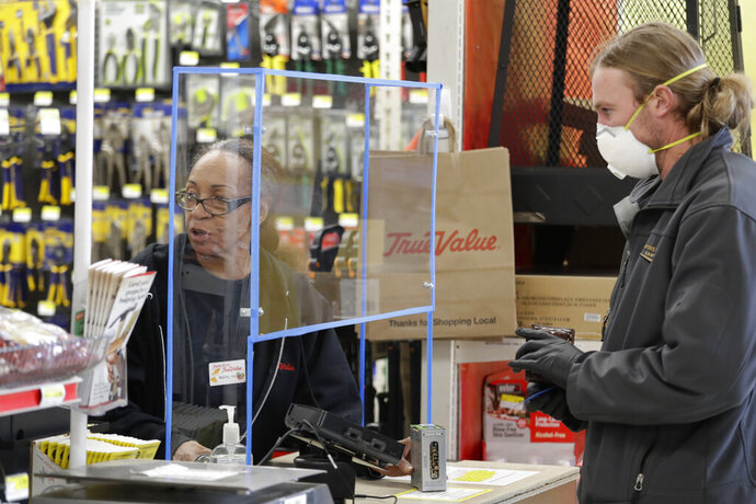 Hardware store clerk Marilyn Larson, left, works behind a plexiglass barrier built a few days earlier by a co-worker to help protect employees and customers during the coronavirus outbreak as customer Phill Kuypers checks-out Wednesday, March 25, 2020, in Seattle. Kuypers wore a mask to take extra precautions while in public because his wife is pregnant. (AP Photo/Elaine Thompson)