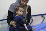 In this Monday, March 5, 2018 photo, Syrian refugee Sara al-Matoura holds her one-year-old daughter, Eman, as she is prepared for surgery at a hospital in Amman, Jordan. Eman, who has a heart defect, received a life-saving pro bono surgery from doctors sent by the Vatican's Bambino Gesu Hospital. The infant is one of the few lucky Syrian refugees with severe medical conditions to get the needed treatment. Dozens more are left untreated each month because of funding constraints in overwhelmed refugee host countries in the region. (AP Photo/Raad Adayleh)