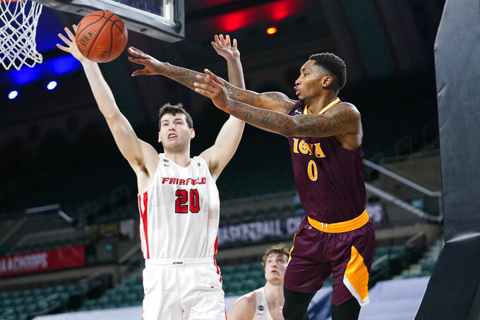 Iona's Berrick JeanLouis (0) passes the ball against Fairfield's Zach Crisler (20) in the first half of an NCAA college basketball game during the finals of the Metro Atlantic Athletic Conference tournament, Saturday, March 13, 2021, in Atlantic City, N.J. (AP Photo/Matt Slocum)