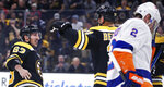 Boston Bruins center Patrice Bergeron, center, is congratulated by teammate Brad Marchand, left, after his goal during second period of an NHL hockey game in Boston, Tuesday, Feb. 5, 2019. At right skating past is New York Islanders defenseman Nick Leddy (2). (AP Photo/Charles Krupa)
