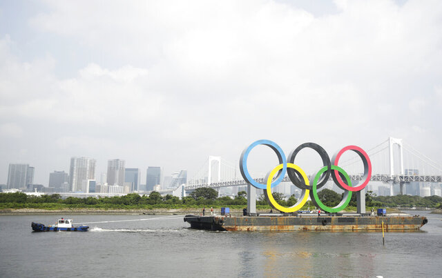 "A tugboat moves a symbol installed for the Olympic and Paralympic Games Tokyo 2020 on a barge moved away from its usual spot off the Odaiba Marine Park in Tokyo Thursday, Aug. 6, 2020. The five Olympic rings floating on a barge in Tokyo Bay were removed for what is being called ""maintenance,"" and officials says they will return to greet next year's Games. The Tokyo Olympics have been postponed for a year because of the coronavirus pandemic and are to open on July 23, 2021. The Paralympics follow on Aug. 24. (AP Photo/Hiro Komae)"