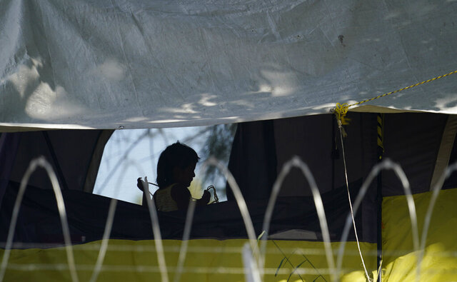 FILE - In this Nov. 18, 2020, file photo, a young girl plays in her family's tent at a camp of asylum seekers stuck at America's doorstep, in Matamoros, Mexico. Increasing numbers of parents and children are crossing the border, driven by violence and poverty in Central America and growing desperation in migrant camps in Mexico. U.S. Customs and Border Protection said Monday, Dec. 14, 2020 that it made 4,592 apprehensions of unaccompanied immigrant children in November, more than six times the figure in April. (AP Photo/Eric Gay File)